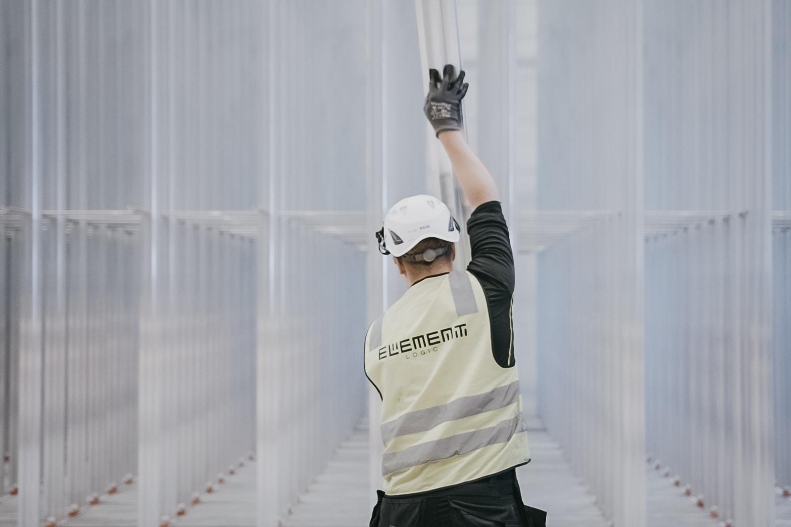 Een man met een helm en een geel vest bouwt het AutoStore-raster op van aluminium pilaren.